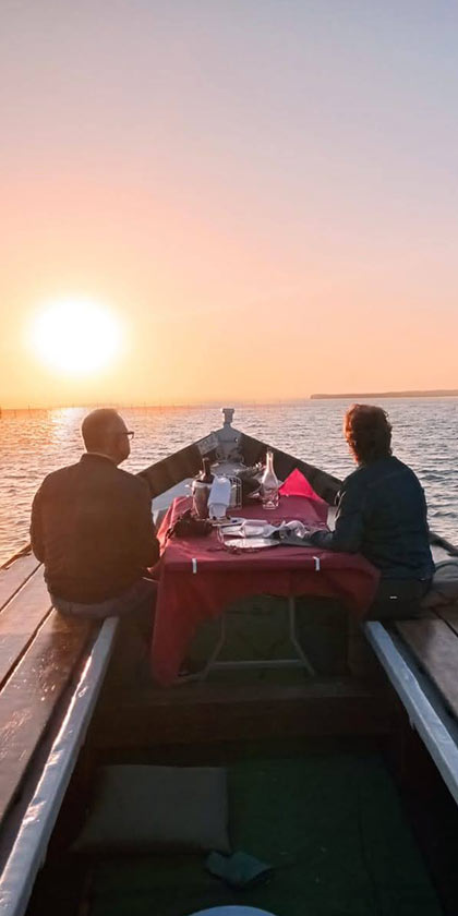 Pareja tomando un aperitivo viendo el atardecer en barca
